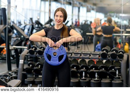 Athletic Woman Performs Strength Exercise With A Barbell In The Gym. Female Athlete Training With Du