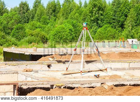Geodetic Equipment Optical Level Mounted On Tripod At The Construction Site. Surveyors Ensure Precis