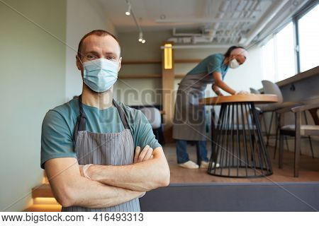 Waist Up Portrait Of Young Male Waiter Wearing Mask And Apron Looking At Camera While Standing In Ca