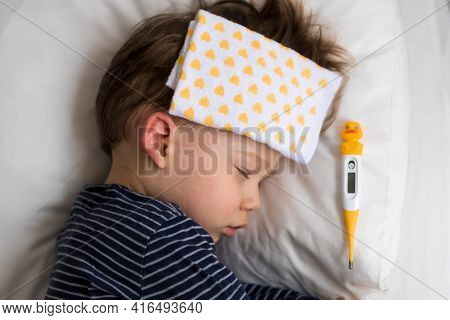 Authentic Portrait Sick Cute Caucasian Little Preschool Baby Boy In Blue Sleep With Compress On Fore