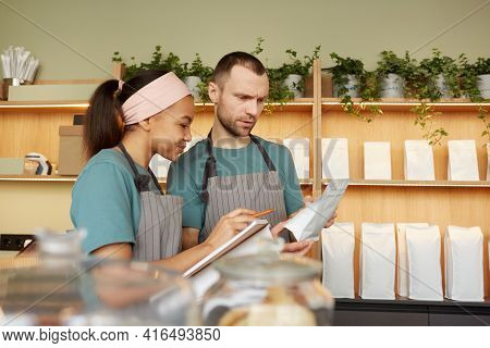 Waist Up Portrait Of Two Young Waiters Wearing Aprons While Doing Inventory In Cafe Or Coffee Shop,
