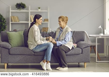 Young Grown Daughter And Old Senior Mother Holding Hands Sitting On Home Sofa