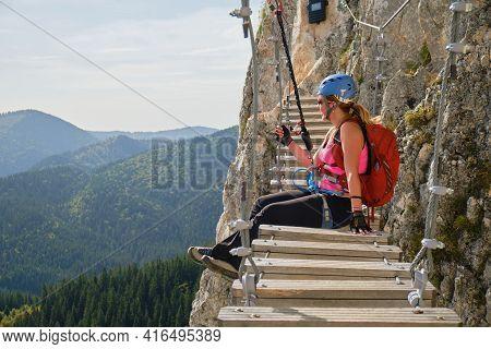 Woman Tourist Admires The View Sitting Down On A Via Ferrata Suspended Bridge At Lacul Rosu, Neamt C