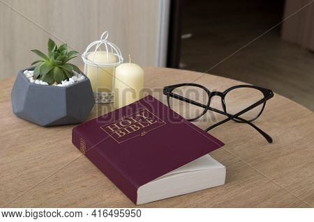 Holy Bible On A Round Table With Candles, Plants And Glasses. Bible Study At Home Concept