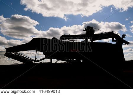 Silhouette Of An Old Threshing Machine Against The Blue Clouded Sky