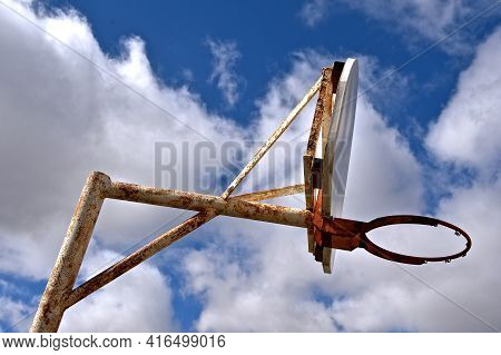 A Crooked Rim And Backboard With A Missing Net Display The Memories Of Outdoor Basketball (black And