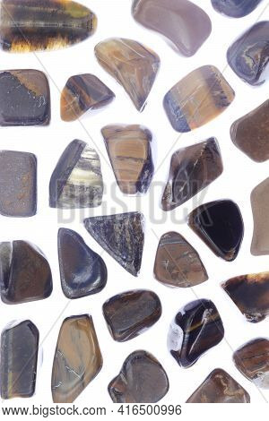 Tiger's Eye Rare Jewel Texture On Light White Isolated Background. Sparse Mineral Pebbles Background