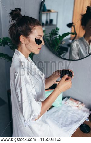 Young Woman Takes Patches From A Jar And Applies Under Her Eyes