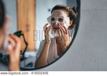 Home Skin Care. A Woman Applies A Sheet Mask To Her Face
