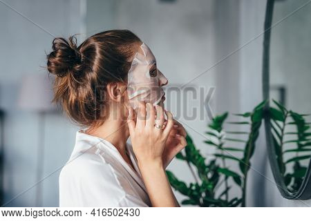 Woman Grooming Her Face In The Bathroom With A Mask On Her Face In Front Of The Mirror