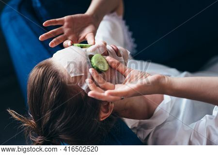Woman Lies On A Couch With A Sheet Mask Over Her Face And Cucumber Slices