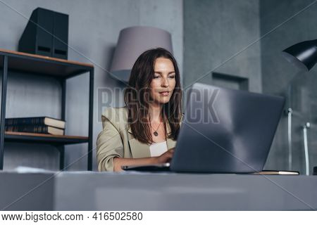 Woman At Her Desk With A Laptop Working From Her Office