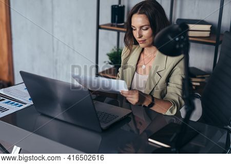 Woman In The Office At Her Desk Working, Holding A Sheet Of Paper In Her Hand.