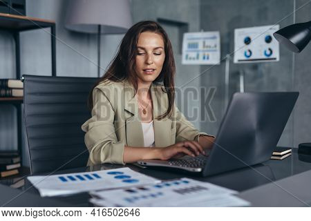 Woman Working With Documents And Laptop Sitting At Her Desk