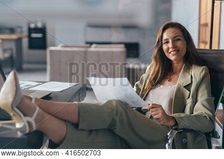 Woman Holding A Sheet Of Paper, Working At Home With Her Feet On Her Desk