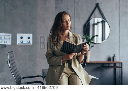 Woman Entrepreneur At Work Reading Notes In A Planner