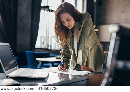 Woman Entrepreneur Stands And Writes Leaning On Desk