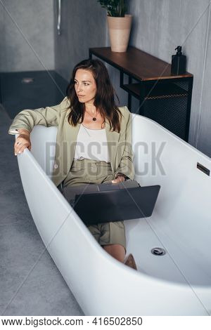 Woman Sitting In A Suit In The Bathtub Pondering Her Work