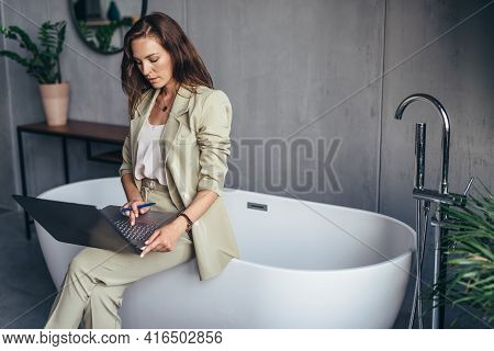 Woman Sits On A Bathtub In The Bathroom And Works With Her Laptop