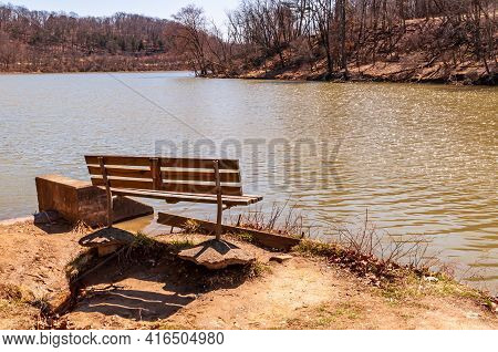 A Park Bench Next To The North Park Lake On A Sunny Spring Day In Hampton Township, Pennsylvania, Us
