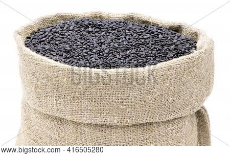 Seeds Of Black Sesame In A Sack Of Isolated On A White Background. Black Sesame In A Burlap Sack. He