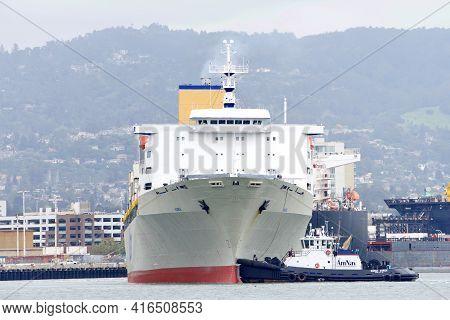 Oakland, Ca - Apr 5, 2021: Tugboat Saarah Avrick Assisting Matson Cargo Ship Manoa To Turn 180 Degre