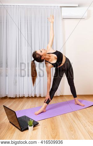 Young Woman Workout, Practicing Yoga In Room, Relaxing Exercise At Home. Interested Girl Watching On
