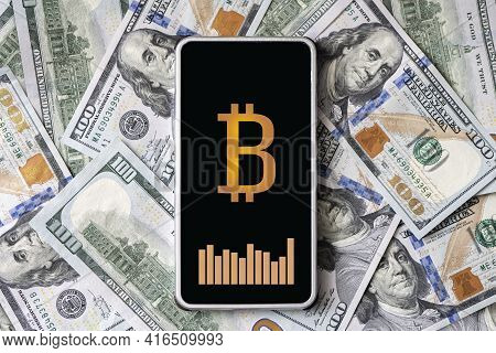 Concept Of Earning Money On Cryptocurrency. A Smartphone With A Bitcoin Logo And A Currency Exchange