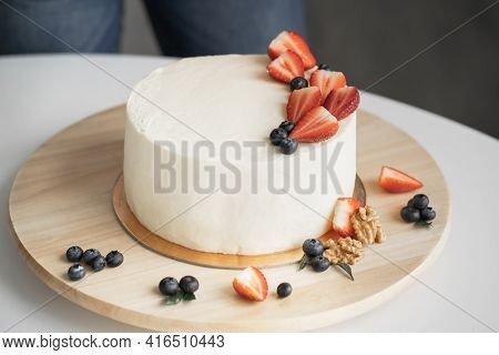 Homemade Cake With Cheese Cream And Fresh Berries. The Pastry Chef Decorates The Cake With Strawberr