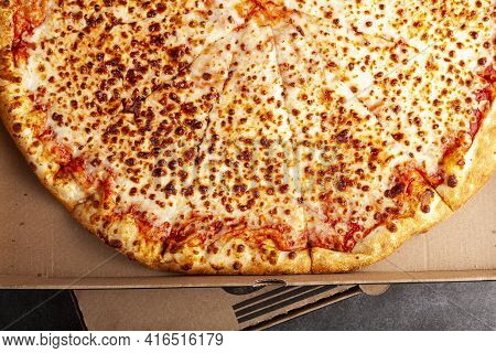 Flat Lay Image Of A Fresh Baked Store Bought Sliced Four Cheese Pizza In Cardboard Pizza Box. It Has