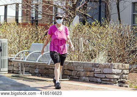 Frederick, Md, Usa 04-07-2021: A Caucasian Middle Aged Woman Wearing Shorts, T Shirt And Sneakers Is