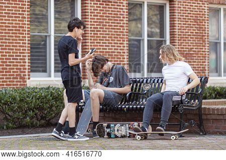Frederick, Md, Usa 04-07-2021: Three Teenager Boys Wearing Casual Trendy Clothes Are Hanging Out In