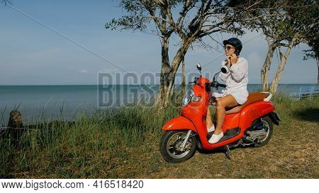 Woman On Red Motorbike In White Clothes Drive On Forest Road Trail Trip. One Girl Caucasian Tourist