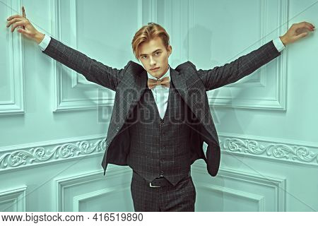 Attractive young man with blond hair poses in elegant classic suit and a bow-tie in white luxury apartments. Men's beauty, fashion.