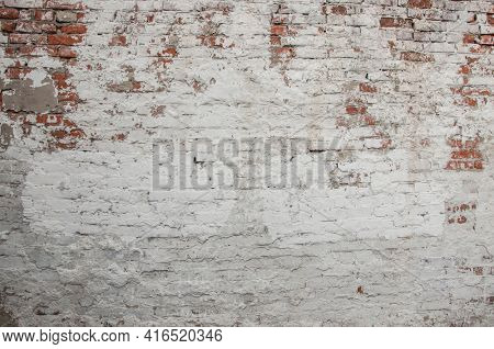 Empty old brick wall texture. Painted distressed wall surface. Grungy wide brickwall. Grunge red stonewall background. Shabby building facade with damaged plaster. Abstract web banner. Copy space.