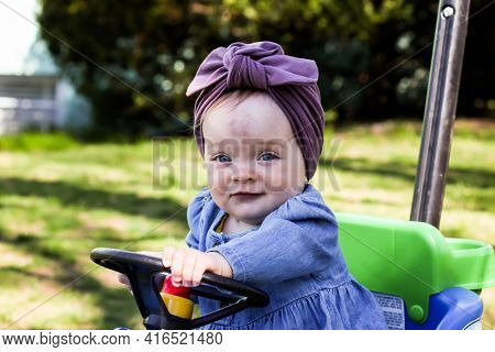 Cute baby girl outdoor in spring time holding toy car wheel