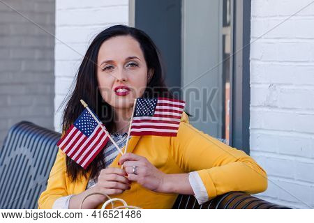 Beautiful young  business woman is looking to camera and holding two little american flag