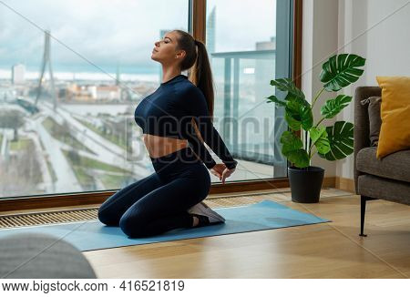 Slender young woman in tracksuit does exercise with hands behind back sitting on mat in room by window with spring city outside