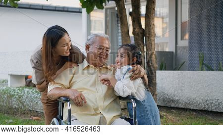 Disabled Senior Grandpa On Wheelchair With Grandchild And Mother In Park, Happy Asian Three Generati