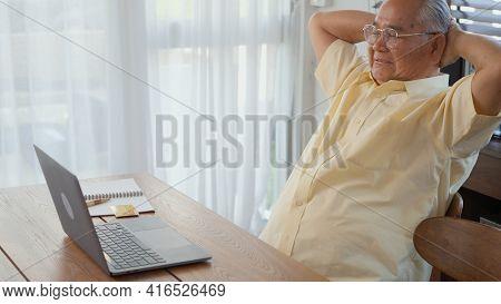 Senior Man Dressed Wear Eyeglasses Sitting On Chair Working On Laptop In Living Room At Home, Happy