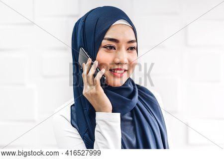 Portrait Of Smiling Happy Beautiful Muslim Woman Relaxing Using Digital Smartphone.young Muslim Girl