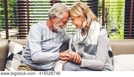 Senior Couple Relaxing And Talking Together Sitting On Sofa In Living Room At Home.retirement Couple
