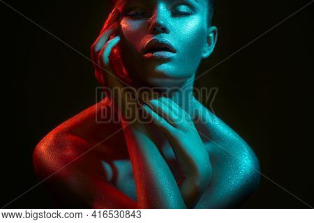Fashion model woman in colorful bright sparkles and neon lights posing in studio, on black, portrait of beautiful sexy girl, trendy glowing sequins make-up. Art design make up. Glitter Vivid makeup