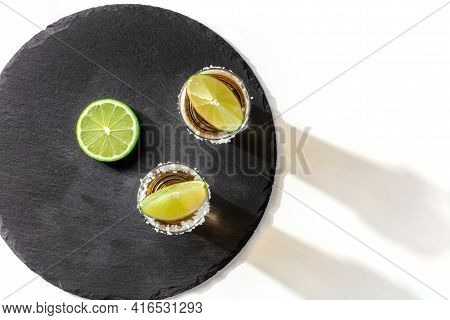 Tequila Shots With Salty Rims And Lime Slices, Top Shot On A White Background
