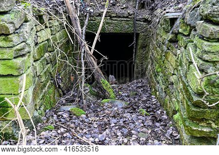 Old Dark Entrace With Stone Walls With Moss