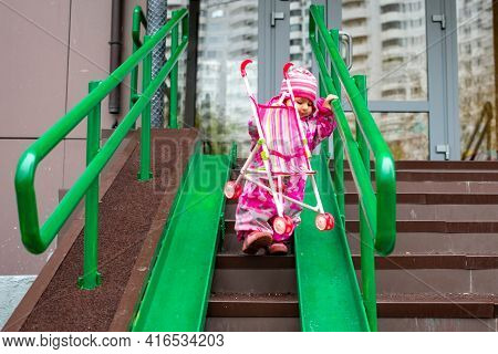Cute Toddler With A Toy Stroller Walks Along Steel Railing Ramp For Wheelchair, Carts And Strollers.