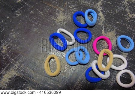 Many Round, Small, Colorful Hair Ties Against A Black Background
