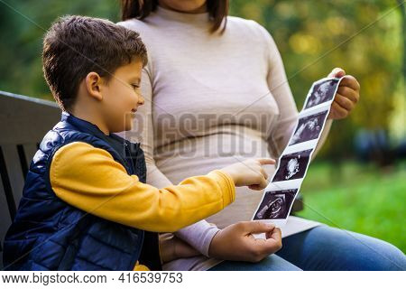 Happy Boy And His Pregnant Mother Are Enjoying Autumn In Park. They Are Looking At X-ray Images Of B
