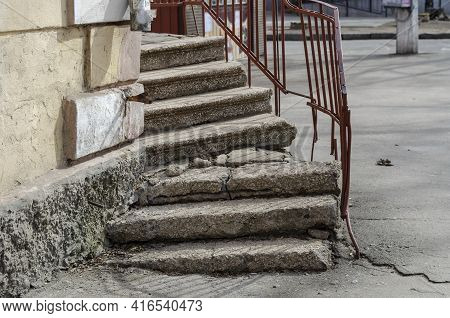 Old Crumbling Stone Staircase With Metal Railings. Rusty Railings Line The Concrete Steps. The Stair