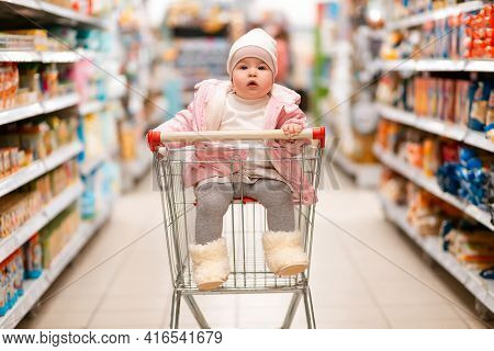 Shopping. A Cute Child Is Sitting In A Shopping Cart In The Middle Of A Supermarket. The Concept Of